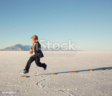 844638658 istock photo Young Business Boy JumpingOn Stepping Stones 844638624