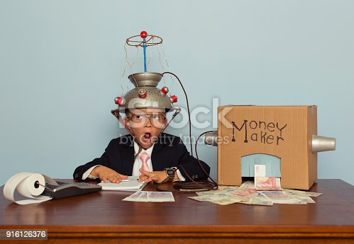A young British boy dressed in business attire wears a homemade mind reading helmet attached to a money making machine. The money machine is making real British Pound Sterling from his head full of ideas. He is surprised at this.