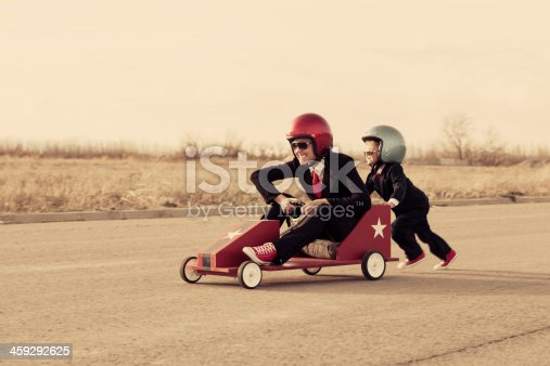 istock Young Business Boy Pushes Woman in Toy Car 459292625