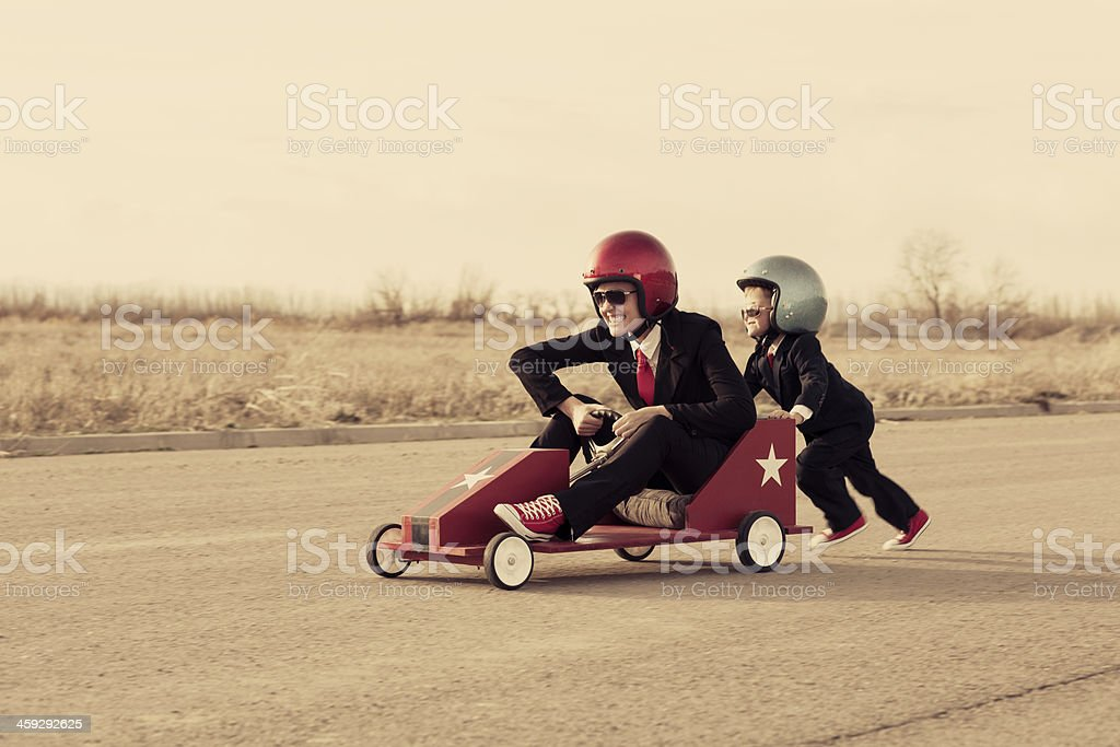 Young Business Boy Pushes Woman in Toy Car stock photo