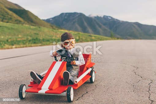 A young business boy dressed in business attire and race goggles sits in a push cart on a rural road in Utah. This business boy loves racing and competing and working for the success of his business. He smiles at the camera before the race starts.