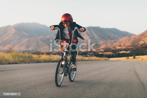 A young business boy is riding his vintage Sting Ray bicycle and trying to makes sales for his business. The boy and businessman is beating his competition. The boy is dressed in business attire, helmet, and racing goggles. He is excited for the success of his new business. Image taken in Utah, USA.