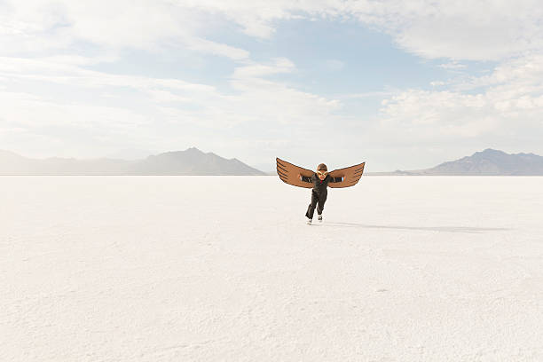 Young Business Boy Running with Cardboard Wings A young business boy dressed in a business suit wearing cardboard wings and aviator goggles is taking his business to the skies. The boy is running on the Bonneville Salt Flats in Utah, USA. Sparse composition. bonneville salt flats stock pictures, royalty-free photos & images