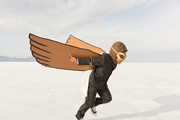young business boy running with cardboard wings - daredevil stock pictures, royalty-free photos & images
