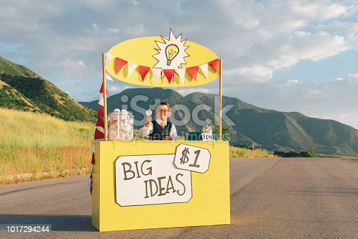 A young boy dressed in business suit sits at a lemonade stand turned into a big business idea stand. He is holding up the next big and greatest idea for sale, and he has lots more of ideas in the form of light bulbs. He is smiling and is excited to make lots of money for his innovative new business. Image taken in Utah, USA.