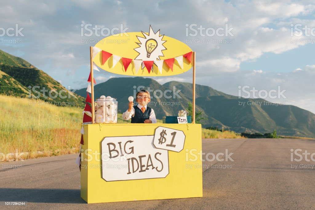 Young Business Boy Runs Big Idea Stand stock photo