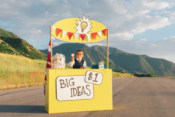 Young Business Boy Runs Big Idea Stand A young boy dressed in business suit sits at a lemonade stand turned into a big business idea stand. He is holding up the next big and greatest idea for sale, and he has lots more of ideas in the form of light bulbs. He is smiling and is excited to make lots of money for his innovative new business. Image taken in Utah, USA. lemonade stand stock pictures, royalty-free photos & images