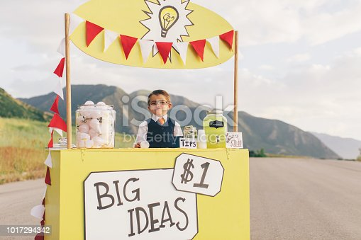 A young boy dressed in business attire sits at a lemonade stand turned into a big business idea stand. He is selling the next big and greatest ideas and he has lots of them in the form of light bulbs. He has a big cheesy smile on his face and is excited to make lots of money for his new business. Image taken in Utah, USA.