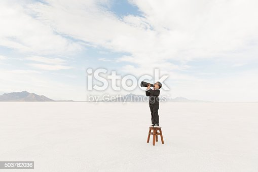 A young boy dressed in business suit yells his message through a megaphone while on the Bonneville Salt Flats of Utah. This important business message is brought to you by a very smart little businessman.