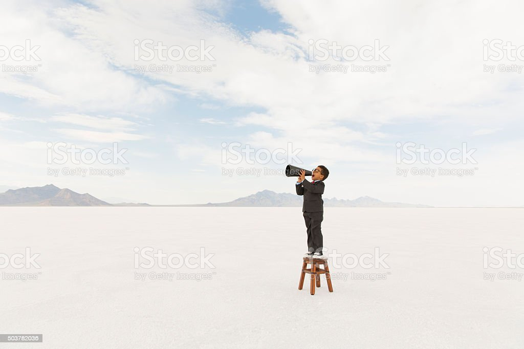 Young Business Boy Standing on Stool Yelling Through Megaphone stock photo