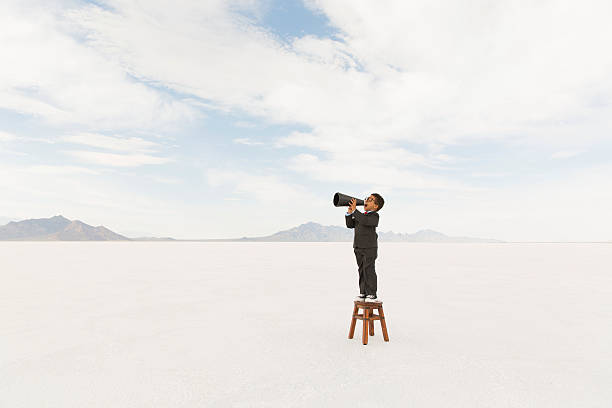 Young Business Boy Standing on Stool Yelling Through Megaphone A young boy dressed in business suit yells his message through a megaphone while on the Bonneville Salt Flats of Utah. This important business message is brought to you by a very smart little businessman. bonneville salt flats stock pictures, royalty-free photos & images