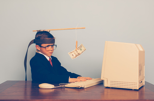 A young boy dressed in a business suit needs some incentive and motivation to get his business project finished while at his work computer. He has dangled money on the end of a stick to keep him on task (carrot on a stick) and to help him succeed with this task.