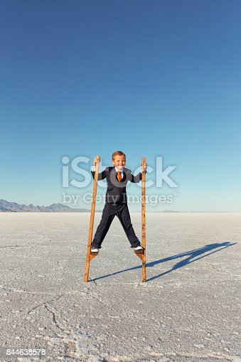 844638658 istock photo Young Business Boy Walking on Stilts 844638578