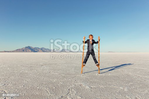 istock Young Business Boy Walking on Stilts 844638614