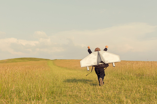 A young business boy is wearing a jetpack running through a grass field in the United Kingdom ready to take his business to the next level.