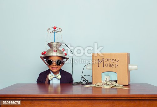 A young boy and businessman feeds his money making machine with great ideas and out comes lots of US Dollars. Bling. Boy dressed in business suit with Benjamin Franklin bow tie. Retro styled. If making money was easy, it would be awesome.