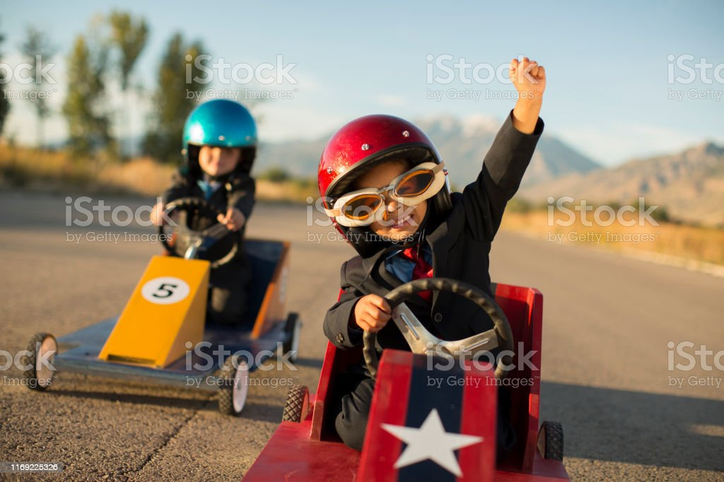 Young Business Boy Winning Car Race A young boy dressed as a businessman wearing racing goggles and helmet raises his arm in victory as he has won the business race and earned glory. He is racing his go cart and favorite car on a rural road in Utah, USA. 4-5 Years Stock Photo