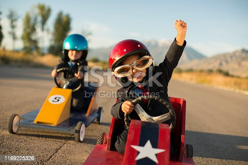 A young boy dressed as a businessman wearing racing goggles and helmet raises his arm in victory as he has won the business race and earned glory. He is racing his go cart and favorite car on a rural road in Utah, USA.