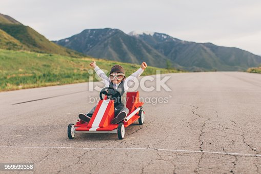 A young business boy dressed in business attire and race goggles in a push cart down a rural road in Utah. This business boy loves racing and competing and working for the success of his business. He gives raised arms at the finish line as he wins.