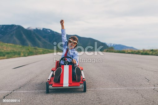 A young business boy dressed in business attire and race goggles races his push cart down a rural road in Utah. He loves racing and competing and working hard for the success of his business. He gives a raised hand in victory at the finish line.