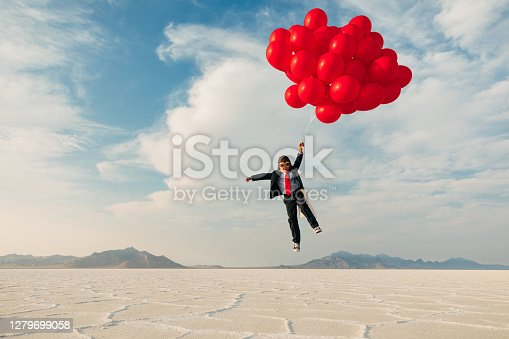 A young boy dressed in business suit, flight cap, and flying goggles holds dozens of red balloons flies his business into the profits atmosphere. Image taken at the Bonneville Salt Flats in Utah, USA.
