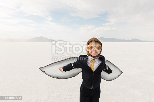 istock Young Business Boy with Cardboard Wings 1154854323
