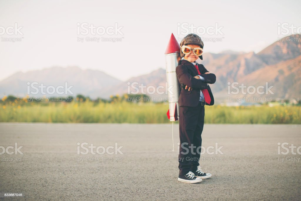 Young Business Boy with Rocket on Back stock photo