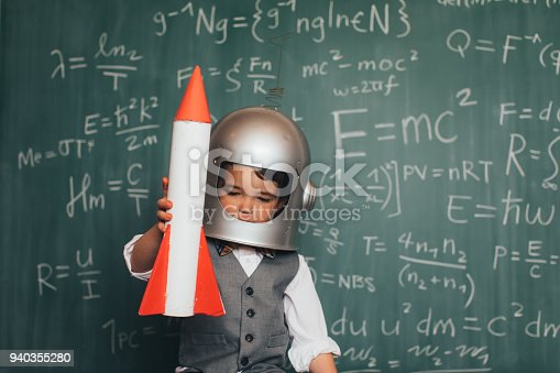 A young business boy dressed in business suit and tie sits in front of a chalkboard full of mathematic equations while wearing an astronaut helmet. He is imagining launching his business into space.