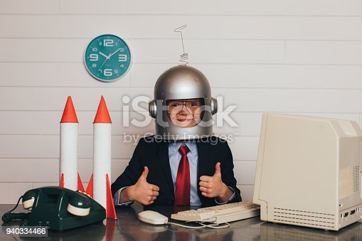 A young business boy dressed in business suit and tie sits at his office desk wearing an astronaut helmet with his two thumbs up. There are rockets on his desk as he is ready to launch his business into space and greater profitability.