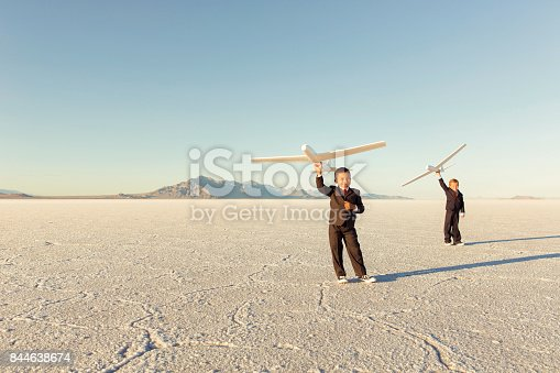 844638658 istock photo Young Business Boys Holding Toy Airplanes 844638674