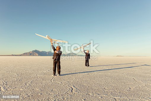 844638658 istock photo Young Business Boys Holding Toy Airplanes 844638698