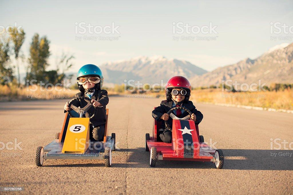 Jeune garçon en costume d'affaires de voitures de course jouet - Photo