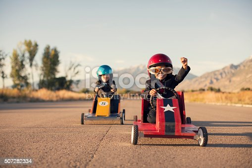 istock Young Business Boys in Suits Race Toy Cars 507282334