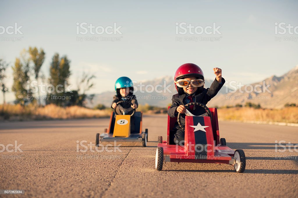 Young Business Boys in Suits Race Toy Cars bildbanksfoto