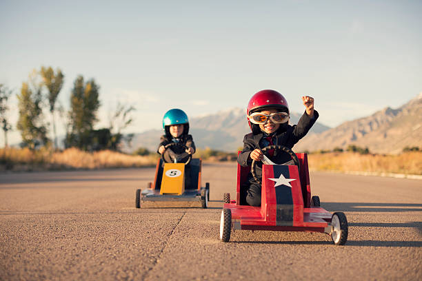 young business boys in suits race toy cars - competitie stockfoto's en -beelden