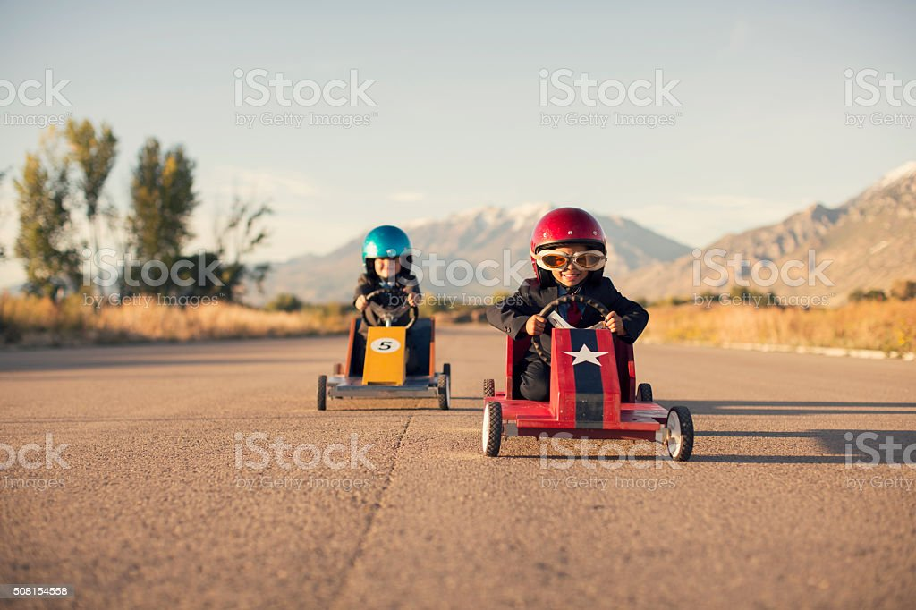 Young Business Boys in Suits Race Toy Cars stock photo