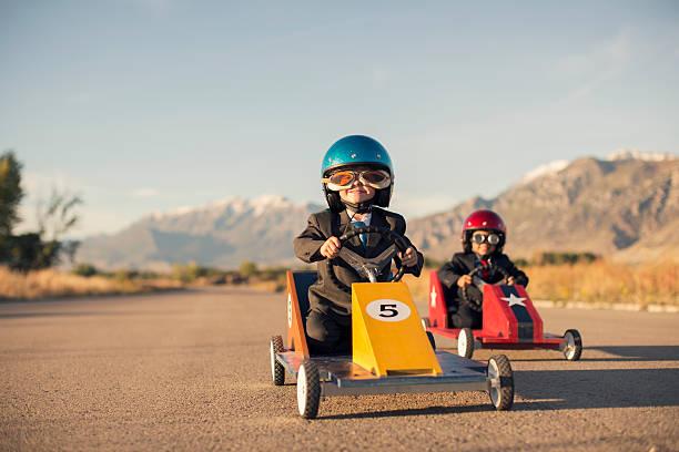 Jovens homens em roupas de negócios de corrida de carros de brinquedo - foto de acervo