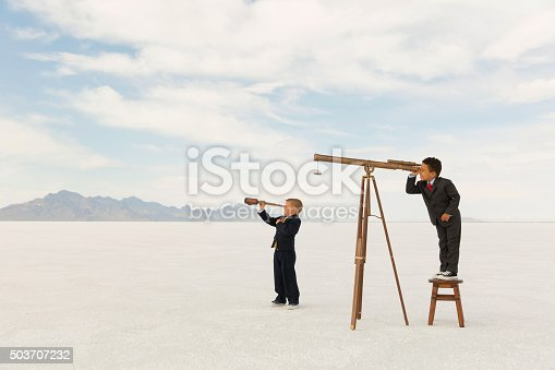 844638658 istock photo Young Business Boys Looking Through Telescopes 503707232