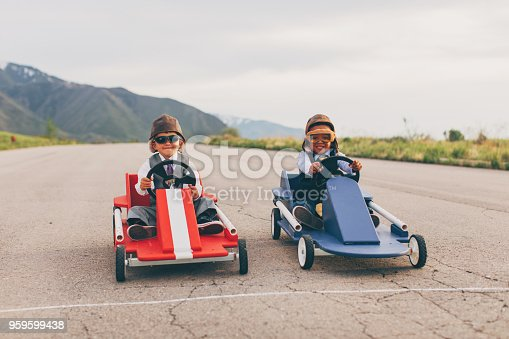 Two young business boys dressed in business attire and race goggles in a push cart down a rural road in Utah. These business children love racing and competing and working together for the success of their business. They smile for the camera at the starting line.