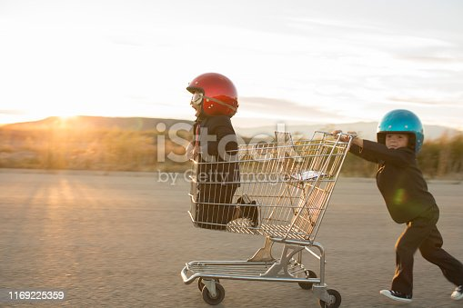 Two young boys dressed as businessmen wearing racing goggles and helmets race a shopping cart on a rural road in Utah, USA. One boy pushes the other business boy while working together towards a finish line.