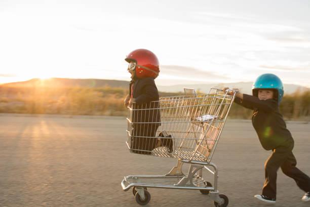 Young Business Boys Racing a Shopping Cart stock photo