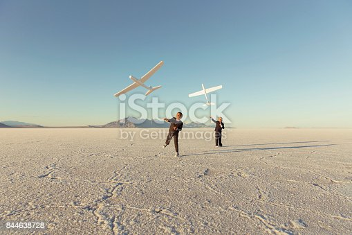 istock Young Business Boys Throw Toy Airplanes 844638728