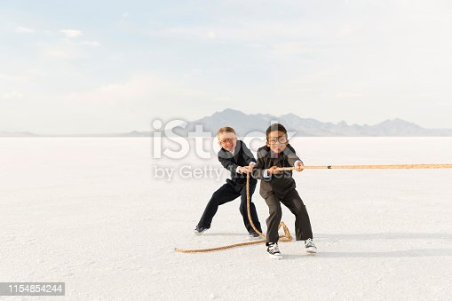 Two young business boys dressed as businessmen tug at a rope in a struggle of tug-of-war. The young business team are working together overcoming all business and market challenges. Business competition goes to the most savvy. Image taken in Utah, USA.