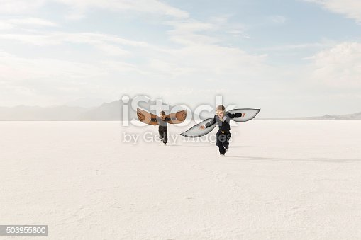 Two young business boys dressed in business suits wearing cardboard wings and aviator goggles are ready to fly their business into the sky. The boys are running on the Bonneville Salt Flats in Utah, USA.