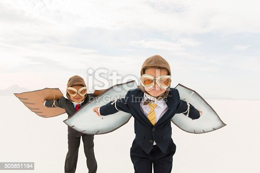 Close up of two young business boys dressed in business suits wearing cardboard bird wings and aviator goggles. They are ready to fly their business into the sky. The boys are standing on the surreal Bonneville Salt Flats in Utah, USA.