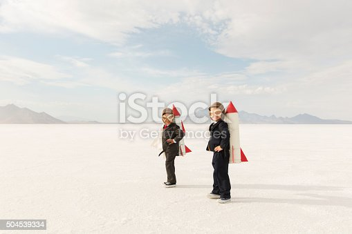 Two young business boys dressed in business suits wearing rockets and aviator goggles are ready to launch their business into the sky. The boys are standing on the Bonneville Salt Flats in Utah, USA.