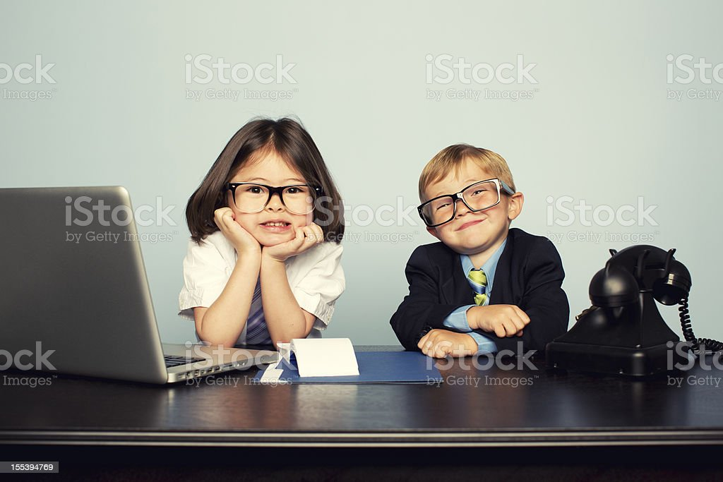 Young Business Children Sitting at Desk with Laptop stock photo