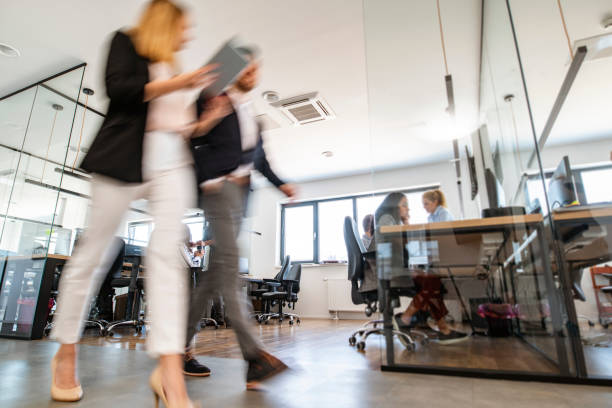 Young Business Colleagues Walking Through Open Plan Office stock photo