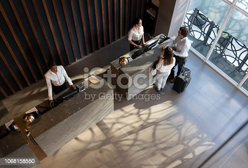 Young business couple checking in at hotel and beautiful receptionist helping them very cheerfully