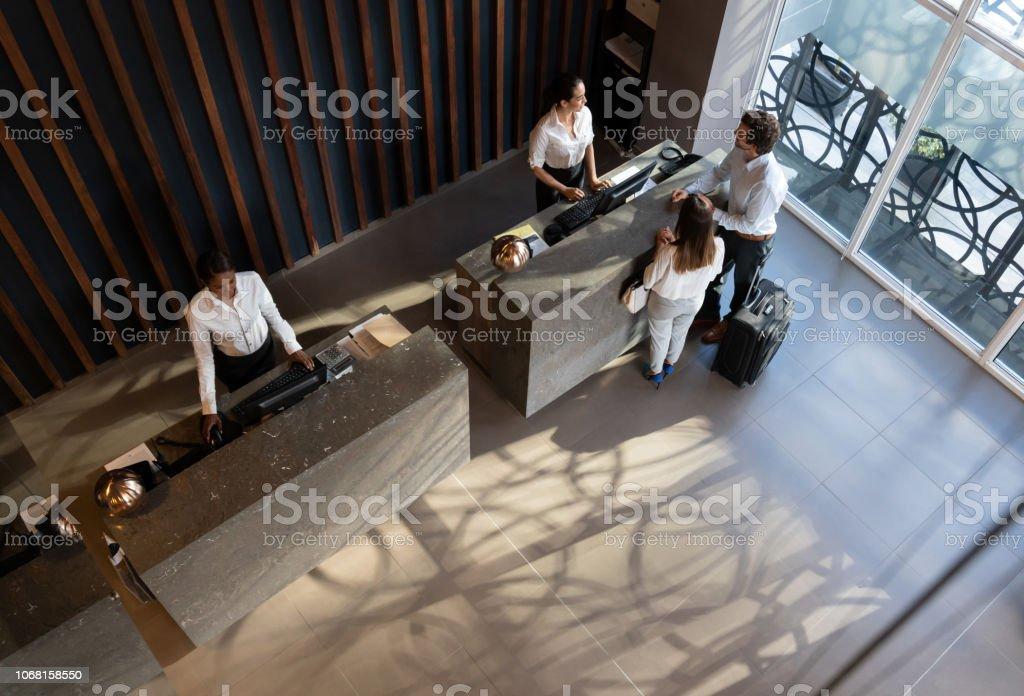 Couple de jeunes entrepreneurs enregistrement à l'hôtel et la belle réceptionniste aidant - Photo